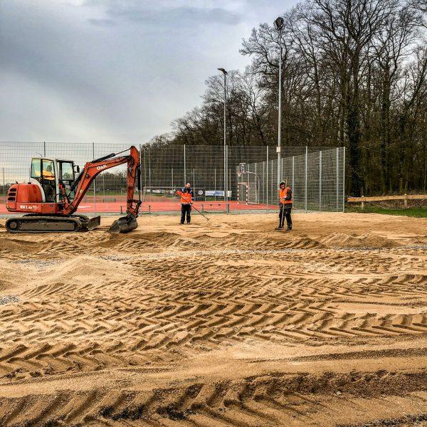 Dolomitsand wird aufwendig verteilt vor der Sportanlage in Hiddingsel.