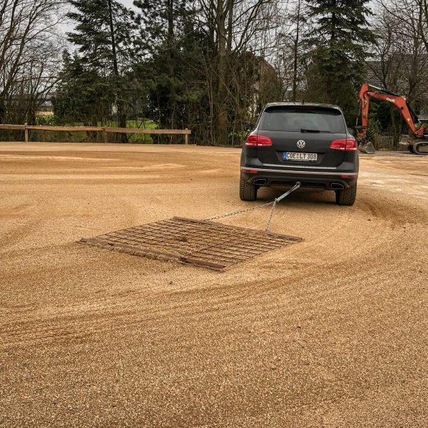 Private PKWs im Einsatz mit einer Matte zum verteilen des Sandes.